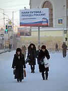 Passanten vor einer Plakatwand zur Duma Wahl von V. Putins Partei Einheitliches Russland in Jakutsk. Jakutsk hat 236.000 Einwohner (2005) und ist Hauptstadt der Teilrepublik Sacha (auch Jakutien genannt) im Foederationskreis Russisch-Fernost und liegt am Fluss Lena. Jakutsk ist im Winter eine der kaeltesten Grossstaedte weltweit mit bis zu durchschnittlichen Wintertemperaturen von -40.9 Grad Celsius.<br /> <br /> Passerby infront of a billboard of Vladimir Putins United Russia party for the Duma elections. Yakutsk is a city in the Russian Far East, located about 4 degrees (450 km) below the Arctic Circle. It is the capital of the Sakha (Yakutia) Republic (formerly the Yakut Autonomous Soviet Socialist Republic), Russia and a major port on the Lena River. Yakutsk is one of the coldest cities on earth, with winter temperatures averaging -40.9 degrees Celsius.