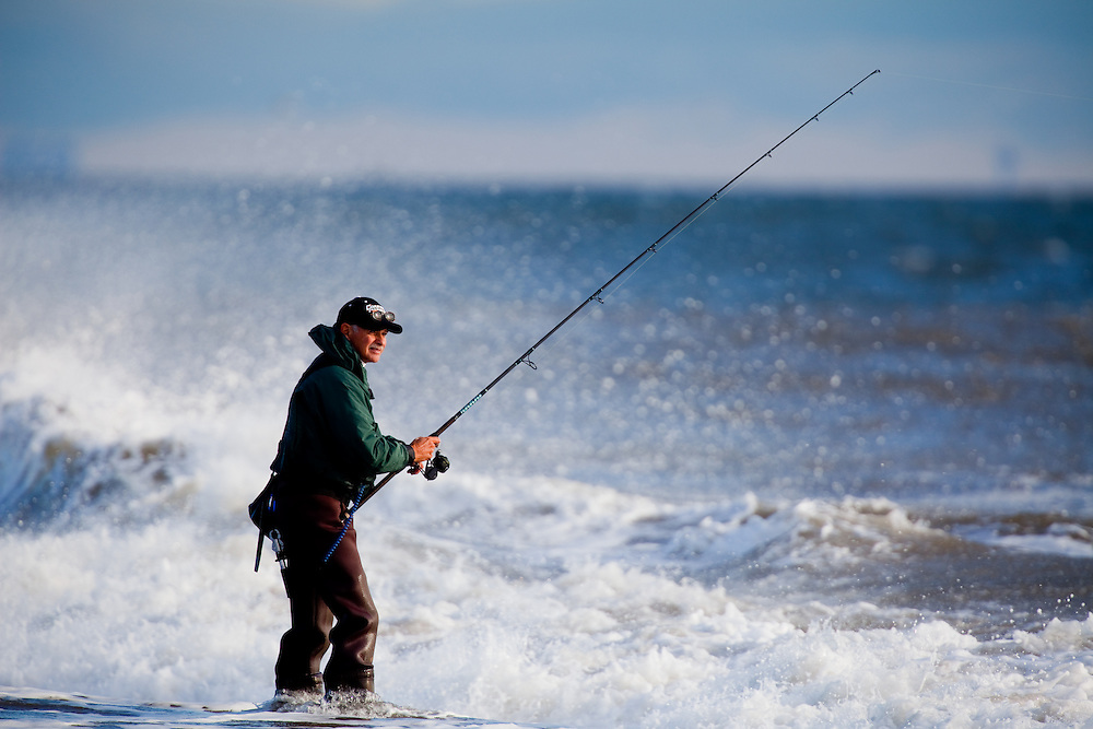 A fisherman working the shoreline at Sandy Hook NJ during durning high surf conditions on a falling tide.   The fall fishing run of striped bass and bluefish is legendary at the park.