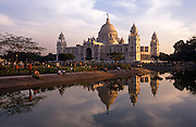 Reflected in the surrounding pond, we see the glorious Victoria Memorial, the beautiful marble structure built by the British still during the days of the colonial Indian Raj. Couples and families gather in the Memorial's grounds to experience the cool air of late-afternoon near the white, domed building. Built between 1906 and 1921, it is a majestic white marble building at the southern end of the Maidan (literally meaning open field, the largest urban park, a large expansive plain in central Calcutta city. Nowadays it is a museum and group activities are being discouraged due to the fears that pollution will damage this fine structure that honours Queen Victoria, then Empress of India.