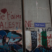 """A street sign says """"Wall Street"""" on the Israel separation wall in Bethlehem. The Israeli West Bank barrier or wall is a separation barrier in the West Bank. Israel calls it a security barrier while Palestinians and many others call it a racial segregation or apartheid wall. At a total length of 708 kilometres (440 miles) upon completion, the border traced by the barrier is more than double the length of the Green Line, with 15% running along it or in Israel, while the remaining 85% cuts at times 18 kilometres (11 miles) deep into the West Bank, isolating about 9.4% of it, leaving an estimated 25,000 Palestinians isolated from the bulk of that territory."""