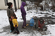 Roma children collect water from a nearby standpipe, they live in a squat in the snow in one of the largest Roma encampments 'bidounvilles' outside Paris. Winter, Sarcelles, Paris suburbs, France<br /><br />Eastern european Roma migrants, often from Romania and Bulgaria, searching for better opportunities, they move near to western european cities. They typically are poor and live in squats, here around the periphery of Paris, in the suburbs 'banlieu' where they typically build ramshackle homes from recycled wooden panels and corrugated iron, or sometimes benders made from branches covered in tarpaulins. They live in woods and forest, industrial estates or derelict buildings. Life is especially difficult for them in the harsh conditions of winter and rain. Most of these camps get destroyed by police and Roma are eventually evicted, some deported back home or moving on to build another home. They often survive by recycling metal and electronic goods, selling recycled clothes and objects they find in trash bins, or through begging or playing music on the city streets or inside metro stations. Paris, France