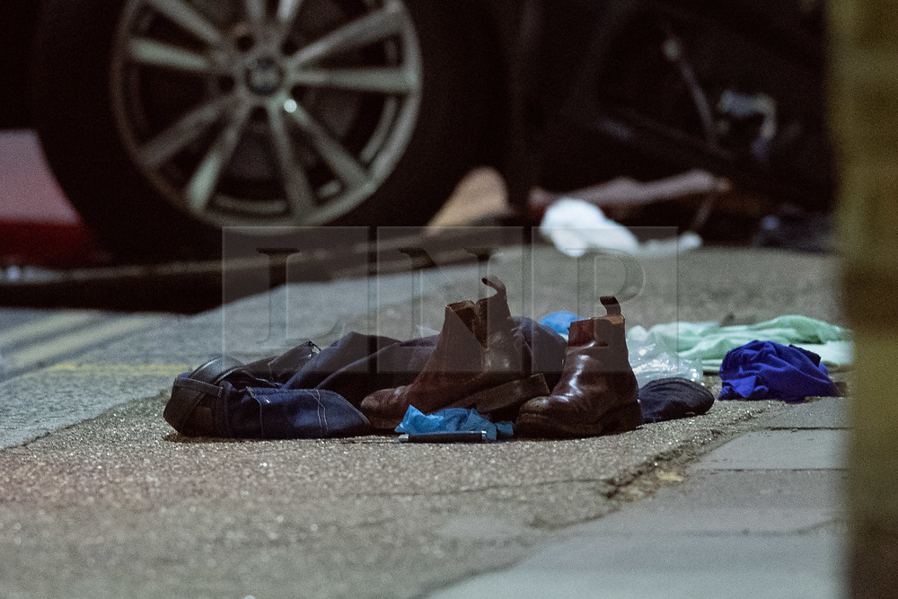 © Licensed to London News Pictures. 08/04/2021. London, UK. Shoes and a knife sit on the pavement on Chiswick High Road following a incident in which a vehicle was stopped by armed police at approximately 22:30hrs on Wednesday 07/04/2021 when police approached the vehicle, officers discovered the lone male occupant had sustained a number of serious self-inflicted injuries. First aid was commenced immediately and the London Ambulance Service were called. The male has been taken to a west London hospital. Photo credit: Peter Manning/LNP