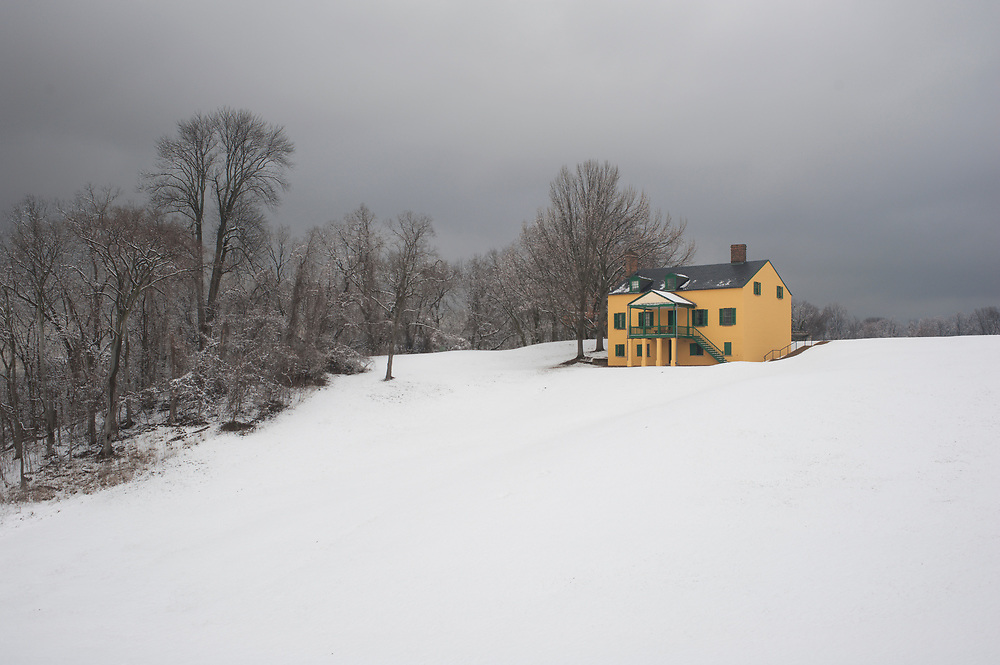 The yellow painted house of the Fort Washington Park visitor center stands in stark contrast with the surrounding snowy landscape in late winter. Fort Washington, MD.