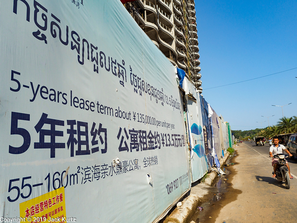 """15 FEBRUARY 2019 - SIHANOUKVILLE, CAMBODIA:  Traffic goes past Blue Bay Resort and Casino, a Chinese development in Sihanoukville. There are about 80 Chinese casinos and resort hotels open in Sihanoukville and dozens more under construction. The casinos are changing the city, once a sleepy port on Southeast Asia's """"backpacker trail"""" into a booming city. The change is coming with a cost though. Many Cambodian residents of Sihanoukville  have lost their homes to make way for the casinos and the jobs are going to Chinese workers, brought in to build casinos and work in the casinos.      PHOTO BY JACK KURTZ"""