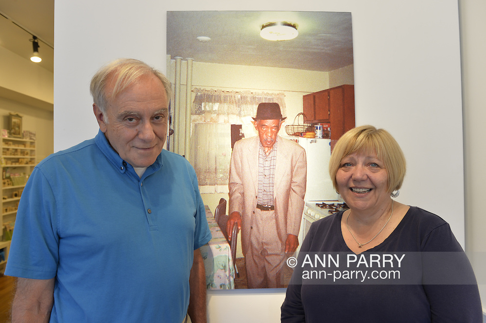 Huntington, New York, USA. August 1, 2015. GEORGE CARRANO and LOIS YOUMANS pose by a photograph by Margaret Wells of a senior man dressed for church, at the Reception for Project Lives exhibition at fotofoto gallery. Over 200 residents throughout 15 New York Public Housing projects were given single use film cameras to photograph what's important to them in their world. The photography project was originated by Carrano and the book Project Lives was edited by Carrano, C. Davis and J. Fisher, with all royalties from its sale to be donated to resident programs at NYC Housing Authority. Youmans is President of the gallery, on the Gold Coast of Long Island.
