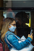 London, United Kingdom, July 10, 2021: A passenger wearing a face protective surgical mask to curb the spread of coronavirus is seen sitting on a public transport bus in London on Saturday, July 10, 2021. The UK reported 34 deaths and 32,367 new cases on Saturday. Over the past week, cases have grown by 30% in the United Kingdom. (VX Photo/ Vudi Xhymshiti)