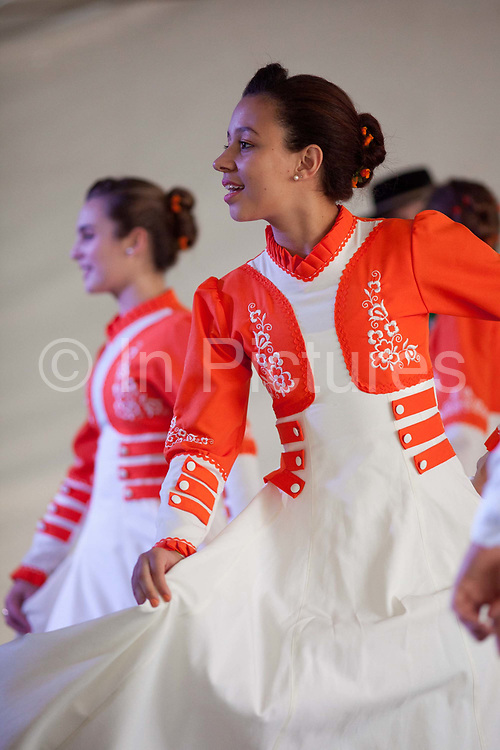 Young women girls teenagers, dancing on stage in couples, wearing traditional Gaucho dancing costumes for a performance. Reponte da Cancao music festival and song competition in Sao Lorenzo do Sul, RIo Grande do Sul, Brazil.