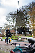 Een man fietst op een OV-fiets langs molen De Ster in Utrecht.<br /> <br /> A man passes a wind mill on his bike in Utrecht.