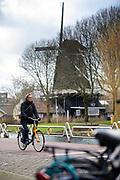 Een man fietst op een OV-fiets langs molen De Ster in Utrecht.<br /> <br /> A man passes a wind mill on his bike in Utrecht.