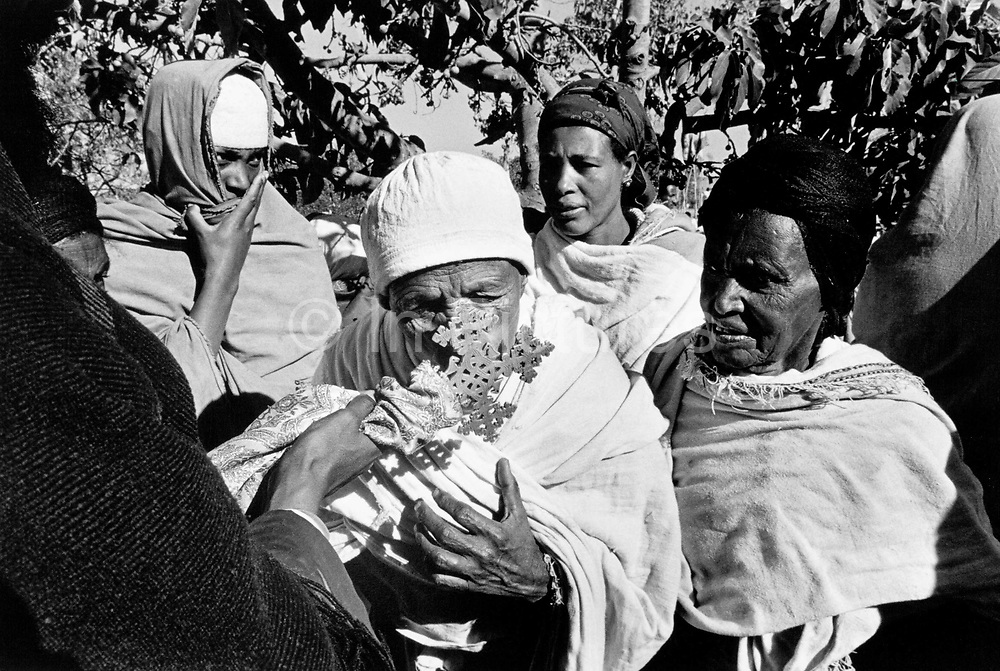 Ethiopian Orthodox pilgrims at Lalibela, Ethiopia. A pilgrim kisses the cross while being blessed during the festival of Timkat (Epiphany). Lalibela in northern Ethiopia is famous for it's monolithic roack hewn churches and is one Ethiopia's holiest cities and a centre of pilgrimage for much of the country.