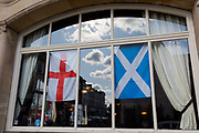 The English Cross of St. George and the Scottish Saltire flags hang together in a pub window, on 2nd October 2019, in Sutton, London, England.  Voters in Sutton voted 53.7% in favour of Brexit during the 2016 referendum.