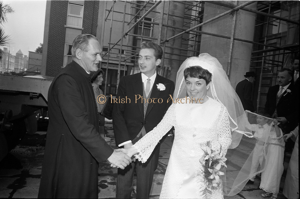 "16/09/1967<br /> 09/16/1967<br /> 16 September 1967<br /> Wedding of Mr Francis W. Moloney, 28 The Stiles Road, Clontarf and Ms Antoinette O'Carroll, ""Melrose"", Leinster Road, Rathmines at Our Lady of Refuge Church, Rathmines, with reception in Colamore Hotel, Coliemore Road, Dalkey. Image shows the Bride and Groom being congratulated by an unknown clergyman after the ceremony."