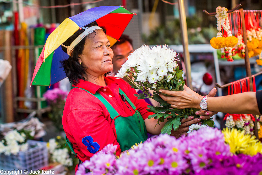 22 OCTOBER 2012 - HAT YAI, THAILAND:      A flower vendor in the market in Hat Yai wearing an umbrella hat because of the rain. Hat Yai is the largest in southern Thailand. It is an important commercial center and tourist destination. It is especially popular with Malaysian, Singaporean and Chinese tourists.     PHOTO BY JACK KURTZ