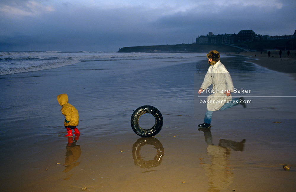 A father chases a runaway tyre (tire) along the wet sand before it crashes into the man's young child, otherwise unaware of the impending impact. Chasing the object is the priority on this winter day at Whitley Bay, a North-Eastern English seaside town. The beach is dark and it has been raining but father and child are enjoying the freedom and common bond during this outdoor game. Waves of the icy North Sea crash onto the seafront and the child is preoccupied with the force of nature and the exhilaration of being outside in the cold. .