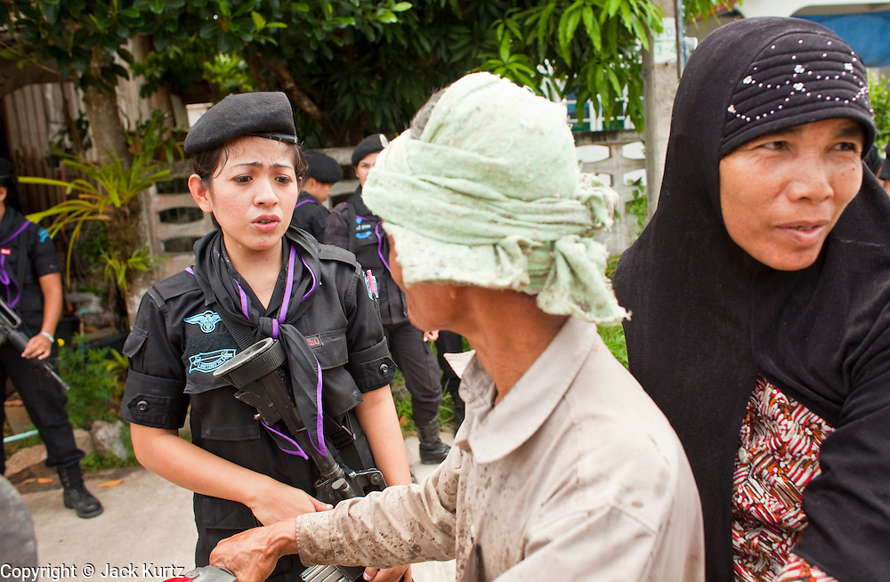 29 SEPTEMBER 2009 -- SAI BURI, PATTANI, THAILAND: Members of the Thai Rangers' womens' unit talk to a Muslim couple on a motorcycle during a security and public outreach program in a Buddhist village in Pattani province, Thailand. The women conduct patrols close to their base and medical assistance to people in nearby villages. The 39 women in the 44th Army Ranger Regiment are the only Thai women seeing front line active duty against Moslem insurgents in Thailand's deep south provinces of Pattani, Narathiwat and Yala. All of the other women serving in Thai security services are employed as office and clerical workers. The Ranger women are based at the Ranger camp in the Buddhist village of Baan Trokbon in Sai Buri district of Pattani province. The unit was formed in 2006 after Muslims complained about the way Thai soldiers, all men, treated Muslim women at roadblocks and during security sweeps. The women are frequently called upon to back up Thai regular army units when they are expected to encounter a large number of Muslim women. At least two of the women have been killed by Muslim insurgents. The unit has both Muslim and Buddhist members. Many of the women in the unit joined after either their fathers or husbands were killed by insurgents.   PHOTO BY JACK KURTZ