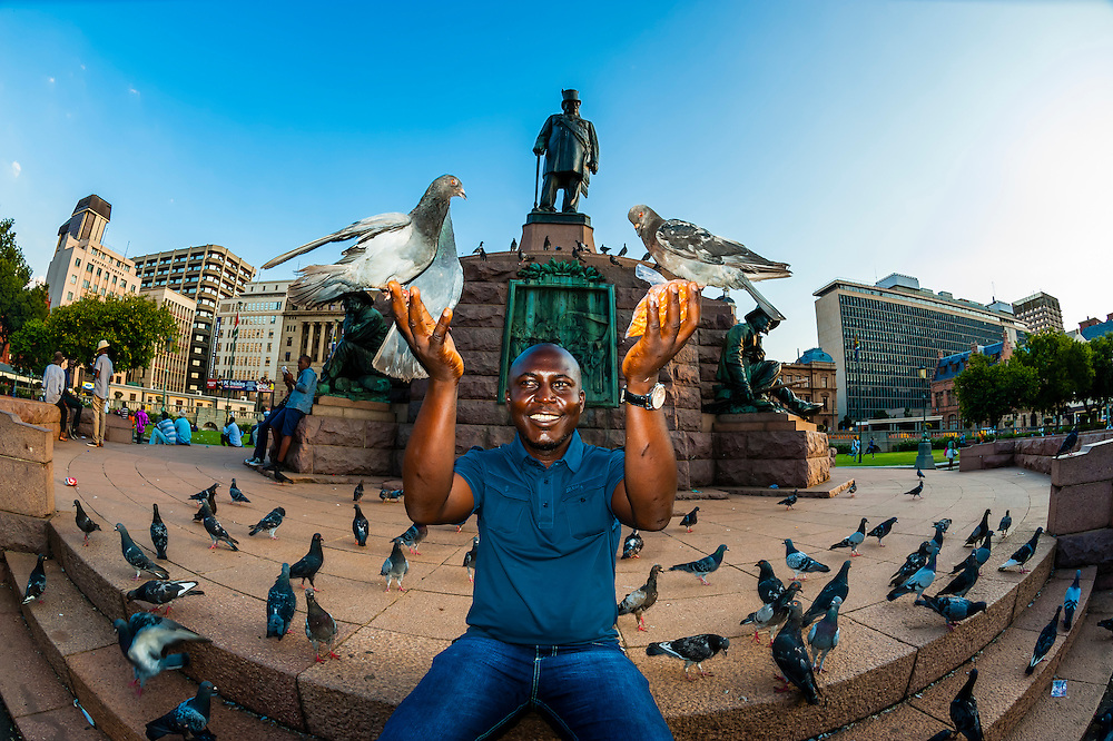 Man feeding pigeons, statue of Paul Kruger, late Boer leader and former president of South Africa in background, Chruch Square (Kerkplein), Pretoria, South Africa.