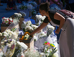"""Marisol Avelar of Boise adds a bouquet of white flowers to a growing pile offered by the Boise community Monday, July 2, 2018 during a vigil at City Hall in Boise, Idaho, USA. A large crowd showed up for the vigil to support the nine stabbing victims from last Saturday night. """"I came to support everybody,"""" Avelar said. """"It's such a tragedy. I have nieces and nephews that age."""" Photo by Darin Oswald/Idaho Statesman/TNS/ABACAPRESS.COM"""