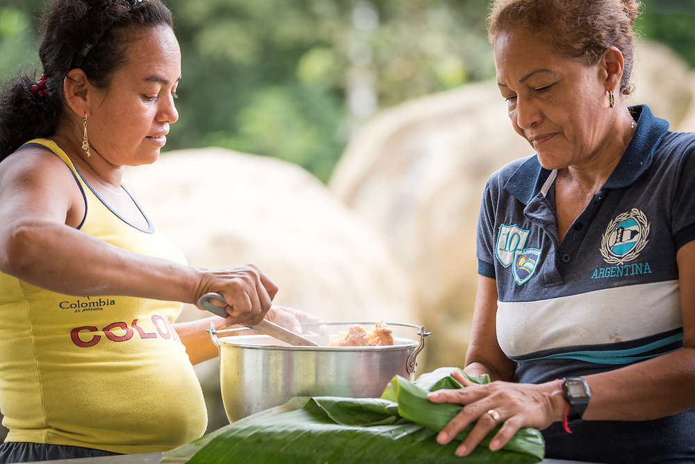 16 November 2018, San José de León, Mutatá, Antioquia, Colombia: Mayerlis (left) serves Aida (right) a meal of sarapa - rice and chicken wrapped in a Cachibou leaf. Following the 2016 peace treaty between FARC and the Colombian government, a group of ex-combatant families have purchased and now cultivate 36 hectares of land in the territory of San José de León, municipality of Mutatá in Antioquia, Colombia. A group of 27 families first purchased the lot of land in San José de León, moving in from nearby Córdoba to settle alongside the 50-or-so families of farmers already living in the area. Today, 50 ex-combatant families live in the emerging community, which hosts a small restaurant, various committees for community organization and development, and which cultivates the land through agriculture, poultry and fish farming. Though the community has come a long way, many challenges remain on the way towards peace and reconciliation. The two-year-old community, which does not yet have a name of its own, is located in the territory of San José de León in Urabá, northwest Colombia, a strategically important corridor for trade into Central America, with resulting drug trafficking and arms trade still keeping armed groups active in the area. Many ex-combatants face trauma and insecurity, and a lack of fulfilment by the Colombian government in transition of land ownership to FARC members makes the situation delicate. Through the project De la Guerra a la Paz ('From War to Peace'), the Evangelical Lutheran Church of Colombia accompanies three communities in the Antioquia region, offering support both to ex-combatants and to the communities they now live alongside, as they reintegrate into society. Supporting a total of more than 300 families, the project seeks to alleviate the risk of re-victimization, or relapse into violent conflict.