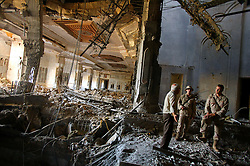 Mowfaq Al-Tai, an Iraqi architect, is seen leading two U.S. soldiers through one of the main rooms inside now partially destroyed Salam Palace in Baghdad, Iraq, Sept. 29, 2003. According to Al-Tai, the Salam Palace is most representative of the design and architecture used in the hundreds of palaces built for Saddam Hussein. Al-Tai was one the the engineers involved in the construction and quality control of the Hussein palaces.