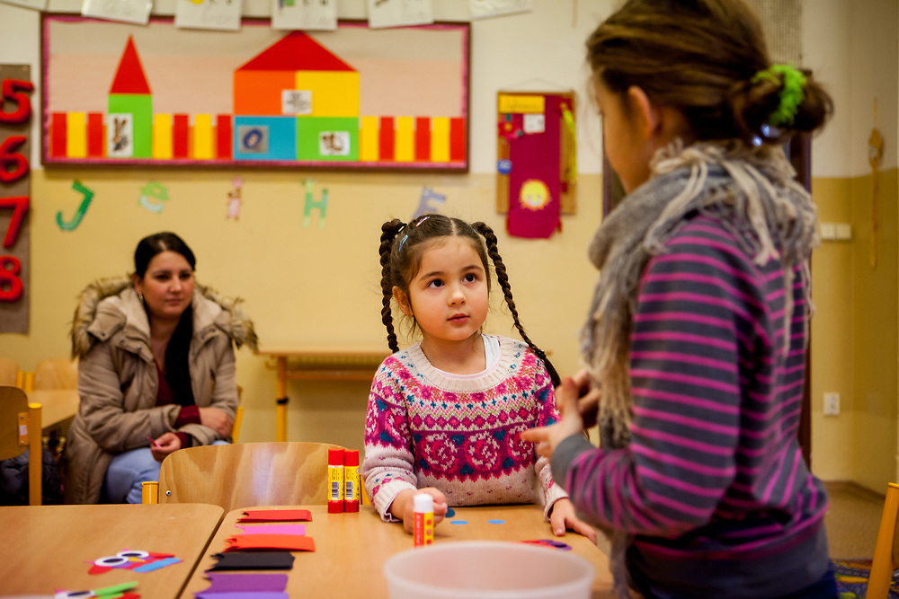 Esther Kroscenova (6) with her mother Daniela Kroscenova (27) in the back waiting for an enrollment examination (test) of daughter Esther who should be a first class pupil in the school year 2016/2017 in a mainstream school in the city of Ostrava, where Roma and non Roma children are educated together. The school is named ZS Chrustova elementary school. The girls are doing some handicraft during waiting for the test.