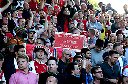 Arsenal fans in the stands hold up a banner honouring outgoing manager Arsene Wenger