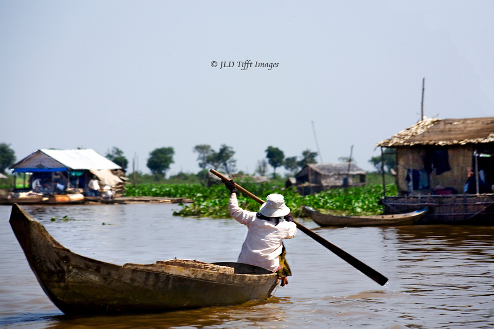Woman paddles homeward in the bow of her dugout canoe.  Two stilt houses are seen in the lake around her.