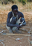 Hadzabe hunter making up fire with sticks. Lake Eyasi, northern Tanzania.