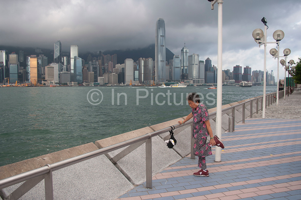 An elderly woman balances on one leg during her morning Tai Chi exercise overlooking Hong Kong Harbour in Hong Kong, China. Many Chinese exercise daily at dawn, resulting in a fit, supple aging population.