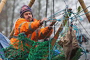 Dan Hooper, widely known as Swampy during the 1990s, hauls a bag from a basket suspended from a bamboo tripod positioned in the river Colne on 8th December 2020 in Denham, United Kingdom. The climate and roads activist had occupied the tripod the previous day in order to delay the building of a bridge as part of works for the controversial HS2 high-speed rail link and a large security operation involving officers from at least three police forces, the National Eviction Team and HS2 security guards was put in place to facilitate his removal.