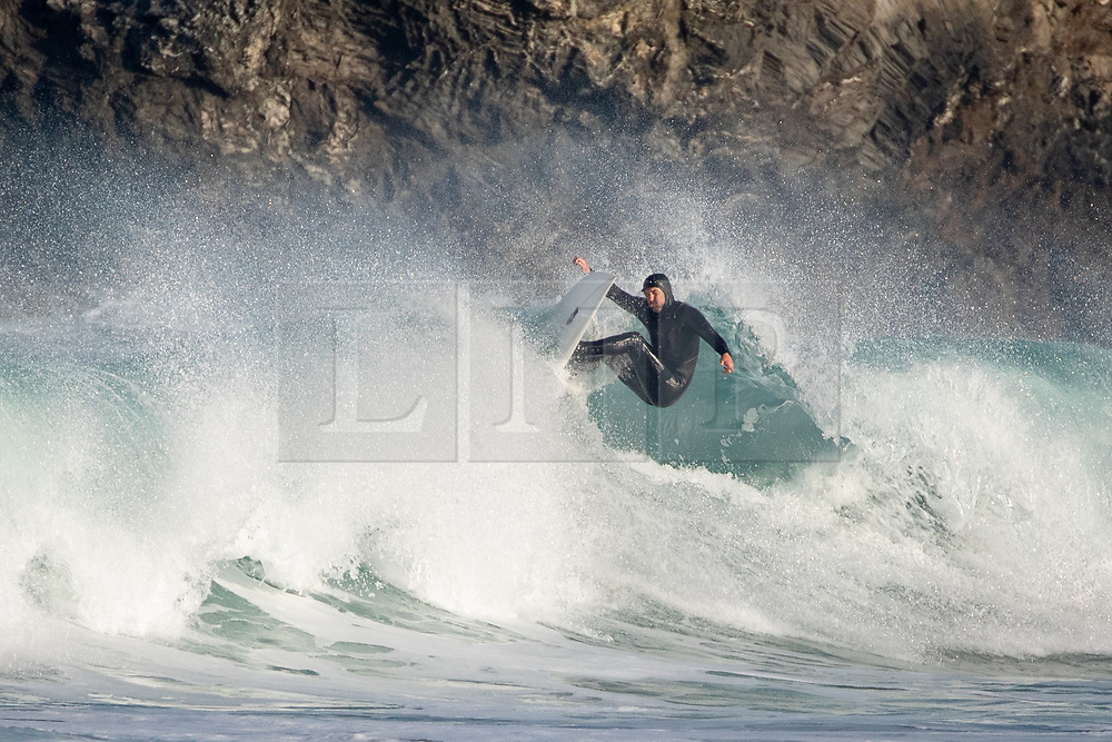 ©2020 Tom Nicholson. 23/04/2020. Padstow, UK. A surfer catches a wave at sunrise this morning near Padstow on the north coast of Cornwall. A period of warm weather is set to continue for the rest of the week. Photo credit : Tom Nicholson