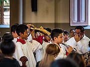 25 MARCH 2016 - BANGKOK, THAILAND: Altar attendants carry a crucifix through the church during Good Friday observances at Santa Cruz Church in Bangkok. Santa Cruz was one of the first Catholic churches established in Bangkok. It was built in the late 1700s by Portuguese soldiers allied with King Taksin the Great in his battles against the Burmese who invaded Thailand (then Siam). There are about 300,000 Catholics in Thailand, in 10 dioceses with 436 parishes. Good Friday marks the day Jesus Christ was crucified by the Romans and is one of the most important days in Catholicism and Christianity.      PHOTO BY JACK KURTZ
