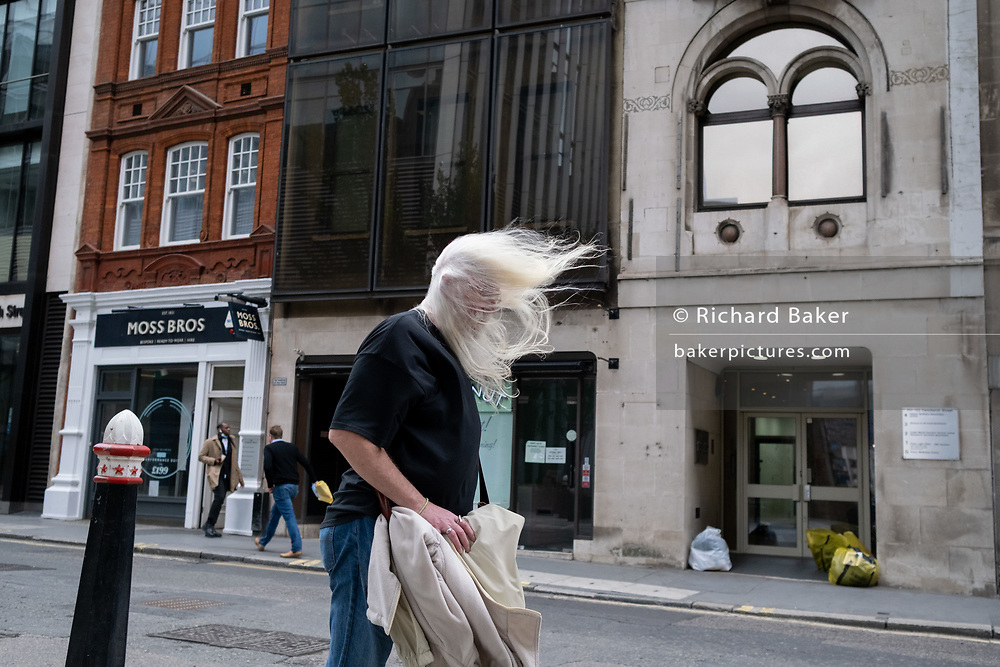 As the Met Office issued alerts for very strong winds across southern England and Wales, a weather system named Storm Francis, a middle-aged man's white hair blows forward to partially obscure his eyesight while walking along Fenchurch Street in the City of London, the capital's financial district, on 25th August 2020, in London, England.