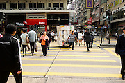 HONG KONG - MARCH 03: A worker pulls styrofoam boxes among the crowd crossing the street in Mong Kok busy neighborhood, on March 3, in Hong Kong. (Photo by Lucas Schifres/Pictobank)