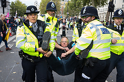 London, UK. 8 October, 2019. Metropolitan Police officers arrest a vicar from Extinction Rebellion who had blocked Whitehall on the second day of International Rebellion protests to demand a government declaration of a climate and ecological emergency, a commitment to halting biodiversity loss and net zero carbon emissions by 2025 and for the government to create and be led by the decisions of a Citizens' Assembly on climate and ecological justice.