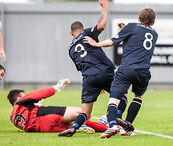 Dumbarton's goalkeeper Jamie Ewings saves from Falkirk's Phil Roberts and Blair Alston.<br /> Dumbarton 1 v 1 Falkirk, Scottish Championship 10/8/2013.<br /> ©Michael Schofield.
