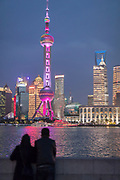 View of tourists looking at the futuristic architecture and skyline of Lujiazui at night, Shanghai, China