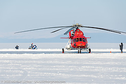 An ice racer goes by the large Russian helicopter that was participating in the Baikal Mile Ice Speed Festival. Maksimiha, Siberia, Russia. Friday, February 28, 2020. Photography ©2020 Michael Lichter.
