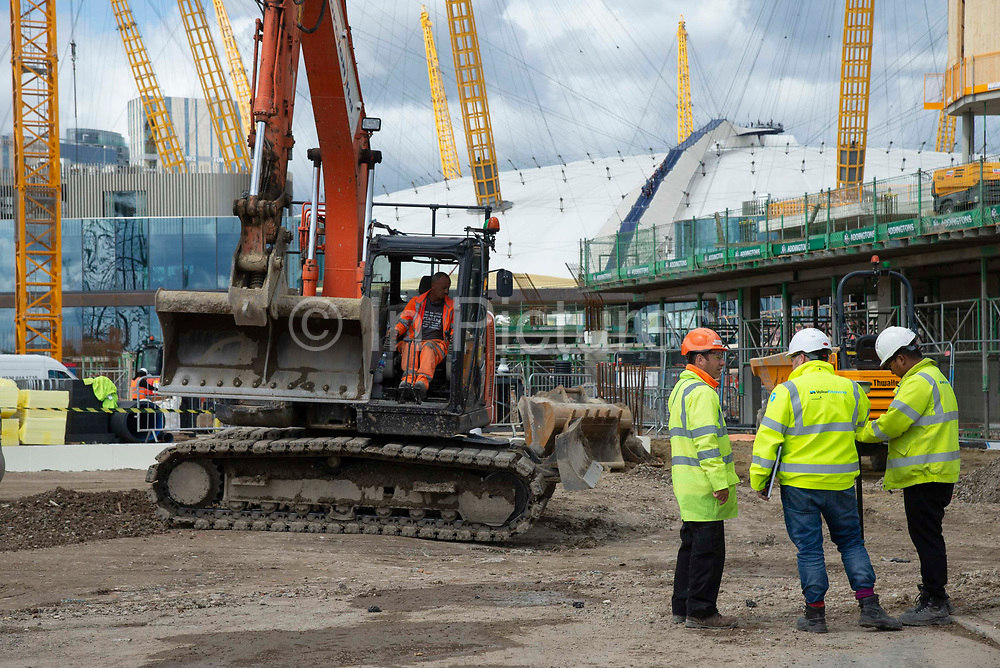 The O2 Arena is seen in the background as a man drives a digger on the  Design District construction site in Greenwich Peninsula in London, United Kingdom on 15th August , 2019. Scheduled to fully open in 2020, developers Knight Dragon Developments Ltd aim to deliver 15,000 new homes. 13,000 new jobs. 7 new neighbourhoods.