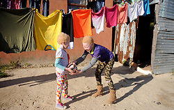 Cape Town- 180830  Linamandla Tyongozi  and Siphosethu Tyongozi from kuyasa Khayelitsha playin with rugby ball. The family are living with albinism. Albinism is a genetic condition. Primarily, albinism affects the hair eyes skin and vision The most common cause of albinism is an interruption in the functioning of the enzyme tyrosinase Picture:Ayanda Ndamane/ African News Agency ANA