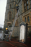 The day after its catastrophic blaze, firefighters continue to assess fire damage from their ladders, to the Queens official residence at Windsor Castle, on 20th November 1992, in London, England. The most northerly corner of this old building that caught fire in a private chapel on the first floor of the north-east wing. Spreading quickly, damaging St Georges Hall, which is often used for banquets. In all, one hundred rooms were damaged in the fire and intense public debate was sparked about whether the taxpayer should foot the repair bill, as the castle is owned by the British Government and not the Royal Family. But the Queen agreed to meet 70% of the costs, and opened Buckingham Palace to the public to generate extra funds. The £40m restoration took five years. Windsor is the largest inhabited castle in the world and partly dates to the time of the Norman King William the Conquerer.