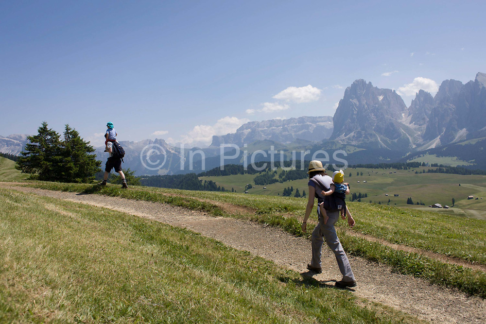 Hikers on the Alpe di Siusi (German: Seiser Alm) plateau, above the South Tyrolean town of Ortisei-Sankt Ulrich in the Dolomites, Italy. Walking along one of the dozens of paths, these hikers enjoy panoramic views of the peaks that envelope the location.  The Alpe di Siusi is the biggest high-alpine pasture in Europe with a surface of 57 km² and its altitude range from 1680 to 2350 m above sea level. This high-alpine pasture is located in the heart of the Dolomites surrounded by the Sasso Lungo Mountain Group, the Sciliar Nature Park, and the Catinaccio Mountain Group, the Northern Alps and the Sciliar Mountain Massif with Santner Peak.