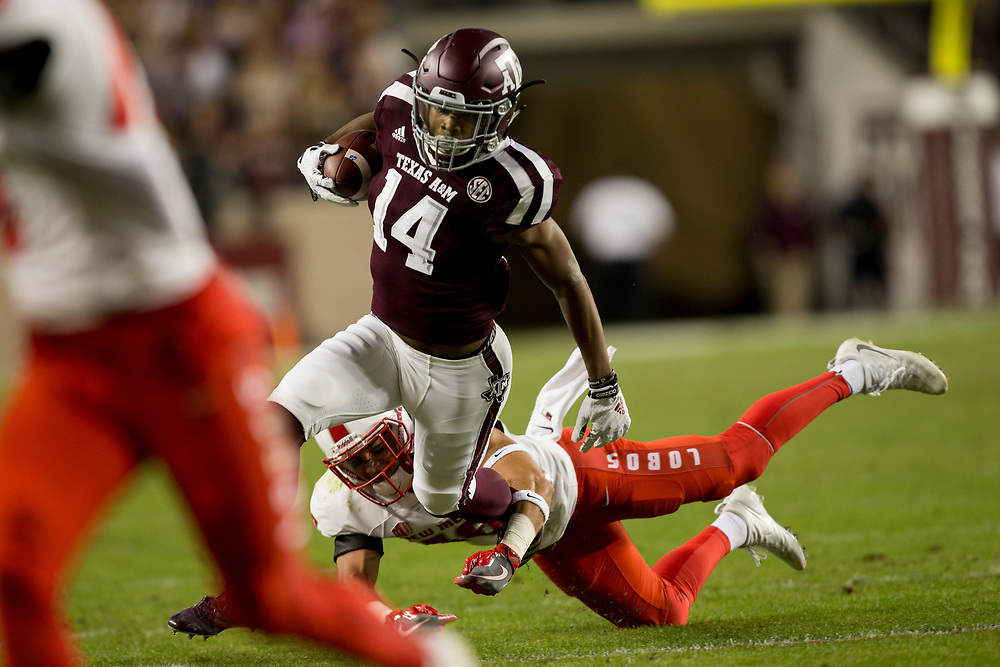 Texas A&M wide receiver Camron Buckley (14) avoids a tackle by New Mexico safety Jacob Girgle (16) after a catch and run during the first quarter of an NCAA college football game on Saturday, Nov. 11, 2017, in College Station, Texas. (AP Photo/Sam Craft)