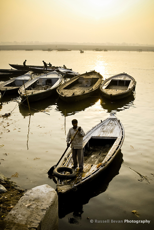 A boatman touts for business after sunrise on the River Ganges in Varanasi, Uttar Pradesh, India
