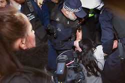 London, March 7th 2015. Following the Climate march through London, masked anarchists and environmental activists clash with police following a breakaway protest at Shell House. PICTURED: A police officer grabs a fallen journalist by her hair before arresting her during a scuffle.