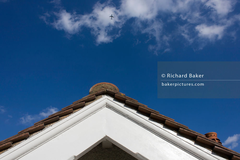 Rooftop view of a suburban Edwardian semi-detached house and overflying airliner in south London.