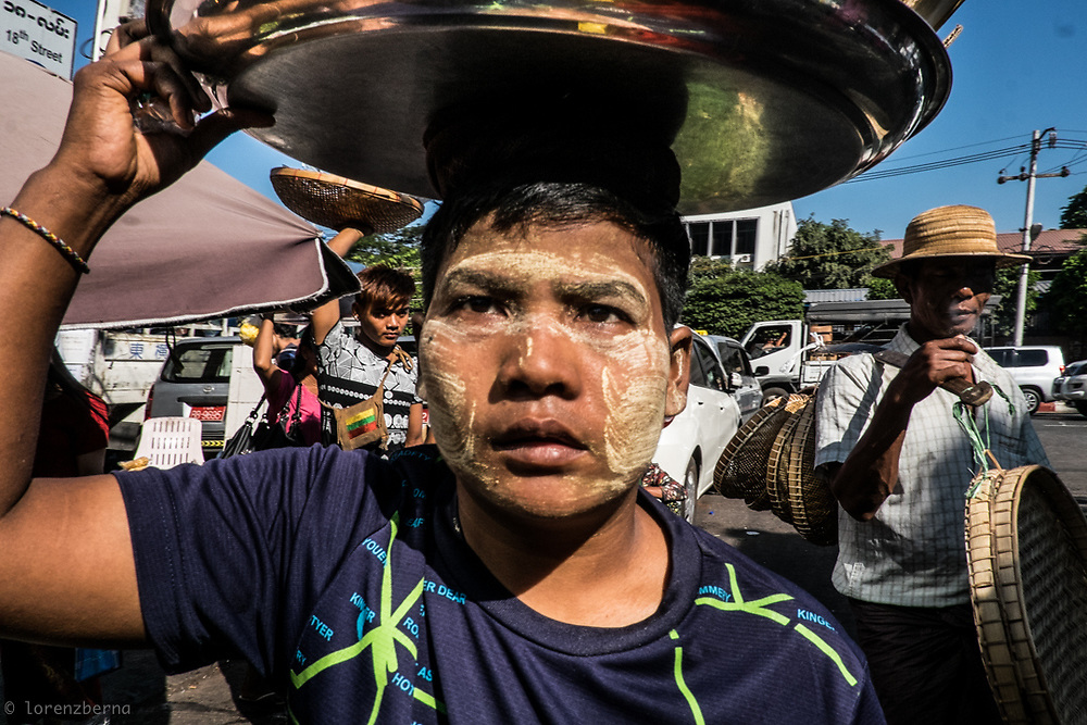 Thanaka wood paste on her face, shield this street vendor from the harsh sun of the tropic in Yangon, Myanmar.<br /> Photo by Lorenz Berna