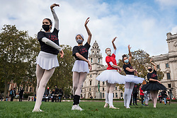 "© Licensed to London News Pictures. 26/10/2020. LONDON, UK.  Ballet dancers perform during ""Survival in the Square"", on day one of a week long series of creative taking place each day in Parliament Square.  The events is organised by #WeMakeEvents, an international movement to highlight that the live events sector urgently needs support from local governments to survive the Covid-19 crisis.  Photo credit: Stephen Chung/LNP"