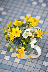 Small arrangement of narcissi, freesias, hellebore and eucalyptus