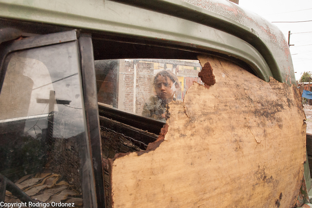 Milagros, 6, sits at the back of a wrecked pickup truck parked in front of her home.