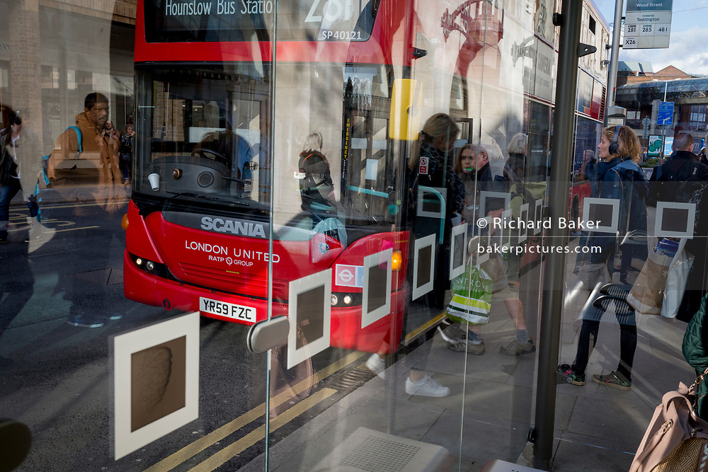 Passengers board a London bus at a bus stop in Kingston, on 7th November 2019, in London, England